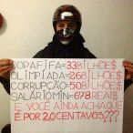 "A masked protestor holds a sign in his home (presumably before or after attending a march in June) contrasting the national minimum wage (about 285 dollars a month) to the billions of dollars of public funds spent on the FIFA World Cup and Summer Olympics as well as billions more lost to corrupt politicians. It ends with ""And you still think this is about 20 cents"" in reference to the 20 cent hike in bus fare that sparked the Free Fare Movement to lead protests in São Paulo (see my previous post on the MPL). [photo found on facebook]"