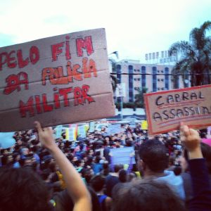 "Signs read ""For the end of the military police"" and ""[Governor] Cabral: Murderer"""