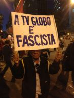 """A man holds a sign calling the Globo media conglomerate fascist. The mammoth corporation (the largest media company in Latin America) supported military rule during the dictatorship (which they kinda, sorta issued a mea culpa for a few years ago), and is routinely accused by everyone on the left of political fascism, racism, misogyny, homophobia and sensationalism. Globo news outlets in turn accuse the protestors of being vandals, trouble makers, looters, and possible-terrorists. One side marches with signs, the other has newspapers, TV channels and radio stations. Guess who reaches a larger audience... When Globo covers protests, they often have to do so in disguise, for they are routinely chased away by protestors shouting insults and chanting """"Globo, fascista, racista, sensacionalista!"""" [photo by Tucker Landesman]"""
