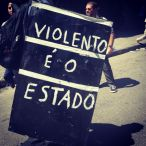 """This protestor carries a placard that doubles as a shield against rubber bullets, flying tear gas and flash bomb canisters, and police truncheons. It reads """"Violent is the State"""" and can be read as part of the growing appeal of anarchist ideology that many of the more radical activists are adopting. Not only does it name the Rio de Janeiro police as perpetrators of violence during the protests (this coincides with a frivolous debate in popular media in which one day they blame the police for a violent clash and the next day they blame the protestors--but mostly they blame the Black Bloc, whom they stop just short of calling terrorists), it also names the State as inherently violent. [photo by Tucker Landesman]"""