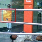 "One of the biggest polemics surrounding the protests is the routine attacks against bank branches by radical groups, and the defence of such tactics by anarchist activists online (commonly on the Black Bloc facebook page). Here we see a child, presumably homeless, sleeping outside the entrance of Itaú Bank. Whoever posted the photo to facebook (I grabbed it off of the Black Bloc facebook page) drew a red box around a sign that reads, ""All children have the right to learn to read and write,"" highlighting the ironic similarity between the boy in the marketing propaganda and the boy sleeping on the pavement. This image is a type of counter discourse used to critique the social system that allows Brazil's economy to boom and banks to post windfall profits, but children are continually denied basic human rights (to housing, to education, to food). Tarnishing Itau's public image in the recent past is a greater than RS$ 18 billion (more than US$7.7 billion) fine for failing to pay taxes. [photo unaccredited on facebook; I have blurred the child's face to protect his identity]"