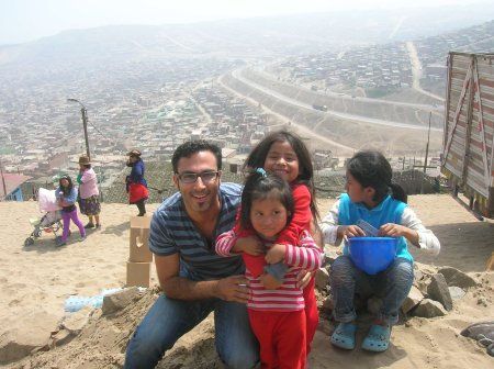 Figure 7 me with excited family kids with the background of sprawling Ventanilla, Peru. Credits: Image of Tal Sustiel