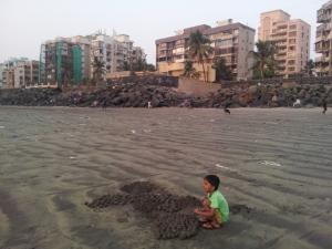 Kid rolling sand balls