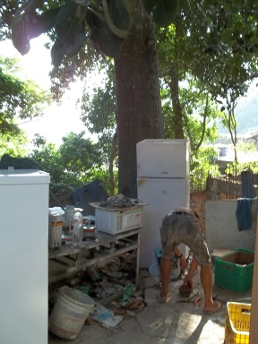On the side of Estrada da Gâvea in Rio, a man carefully dismantles appliances to sort and salvage the various metals.