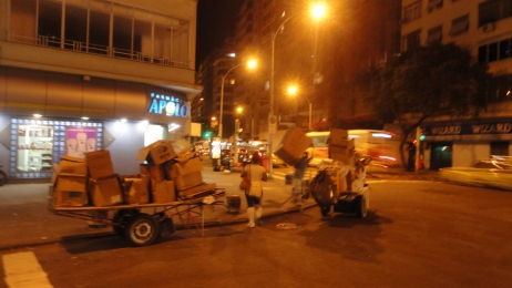About 2 am, a catador gathers recyclable cardboard from the street side waste in Copacabana.